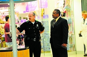 Director of Security Earl Morgan walks the shopping center, shown here talking to Dallas Police Sr. Corporal Jeff Ell. 'It is important to visualize the coverage area in person while looking at the cameras,' says Morgan. 'The best way to do that is to review the areas in person, on a regular basis.'